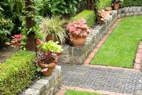 Paths and walls made from reclaimed cobbles, station platform tiles and bricks, and Buxus sempervirens - Box hedge, clay pots with Heuchera and trellis with Clematis - Brocklebank Road, Southport, Lancashire NGS