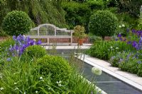 Blue perennial borders edge a water rill that leads to a wooden bench - Geranium pratense 'Johnson's Blue', Iris pseudacorus and Iris sibirica