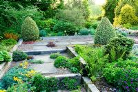 Shallow steps and raised beds constructed with weathered railway sleepers, plants seeded into the gravel path including Geraniums, Tropaeolum polyphyllum and Sempervivums - Ivy Croft, Leominster, Herefordshire, UK