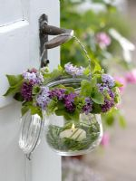 Tealight with wreath of Syringa - Lilac and Alchemilla - Lady's Mantle hung on door handle with candle in the small circle of grass