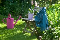 Picking Spring flowers with pink watering can in garden