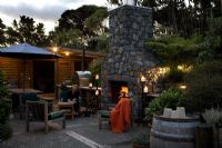 Exterior fireplace and entertaining area. Laurus - Bay trees and Cyathea dealbata - Tree Ferns. New Zealand