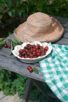 Bowl of cherries on table with sunhat