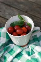 Plums in pottery mug with check cloth