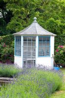 Blue and white summerhouse. Lavandula - Lavender and watering can