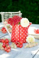 Red and white currants displayed with polka dot jug and flowers on table