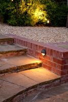 Brick edged stone steps and gravel patio lit up at night. Fargesia nitida - Bamboo
