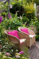 Small garden with wicker chairs surrounded by Digitalis - Foxgloves and Hydrangea - Scheper Town Garden