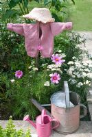 Scarecrow made with chlids pink cardigan in flower bed with Achillea and Cosmos