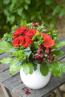 Bouquet of red Roses and Gerbera on old wooden table outdoors
