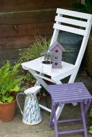 White seat with purple bird house and stool