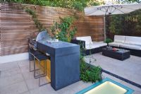 Modern garden with barbecue, built in lighting and dining area