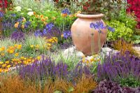 Ornamental urn in colourful summer garden
