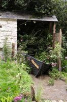 Wooden boat used as planter in rustic outbuilding