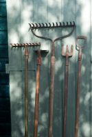 Old garden tools against painted shed door