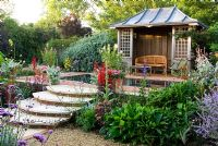 Summerhouse with reflecting pool surrounded by brightly coloured perennials including Lobelia cardinalis, Cleomes, Plectranthus and Aconites - Isle of Wight, UK