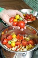 Making home-made mixed tomato chutney - putting ingredients into saucepan
