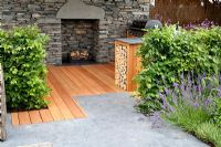 Log storage and dry stone walls with fireplace. Lavandula, Thymus and Fagus - Beech hedge. 'Inside Out'  garden - RHS Tatton Park Flower Show 2011