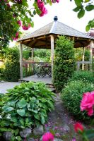 Rosa 'Étude' climbing on pergola, Hosta, Geranium, cobbled stone path,  wooden summer house and decking