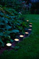 Garden lighting - small zinc candle holders edging a flower bed