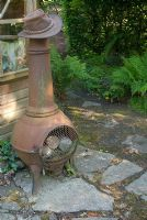 Chiminea by shed and stone path in shaded part of garden