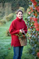 Woman in red jumper carrying wooden basket of mixed Hollies