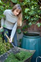 Lady filling compost bin with lawn cuttings