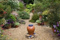 Gravel garden with central terracotta bubble water feature, full of tender perennials and exotics. Fuschia boliviana,  Salvia, Tradescantia sillamontana, Heliotropium arborsecens, Petunias, Buddleja davidii, Isotama axillaris and Bidens - Pine House