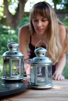 Woman lighting tea light lanterns