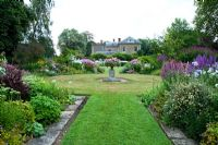 The Sickle Beds, in the formal garden to the west of the house, with central urn and beds full of Phlox, Lythrums, Crinums and other herbaceous perennials - Old Rectory, Pulham, Dorset