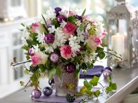 Floral arrangement on kitchen worktop - Narcissus 'Ziva', Rosa, Hedera decorated with purple baubles