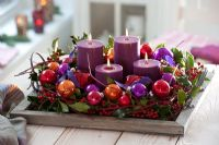 Christmas candles in wooden tray decorated with baubles, Cornus stems and Ilex - Holly berries