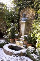 Formal garden with sculpture and water feature in snow - The Old School House, Great Bentley, Essex in January