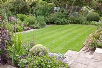Flowerbeds and paving surrounding lawn