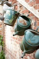 Watering cans and buckets as a decoration on brick wall