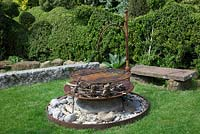 Rusty firepit sitting on a large stone boulder, with fir cones and kindling