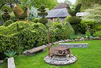 Topiary garden including Yew birds, wedding-cake tiers and crowns. Firepit atop large flint stone with kindling
