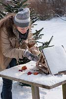 Woman placing apples on a bird table