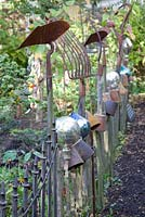Rustic fence decorated with old gardening tools and equipment