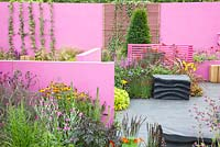 Modern garden with screens. Planting includes Coreopsis 'Early Sunrise', Delphinium 'King Arthur', Achillea 'Walther Funcke', Crocosmia 'Lucifer', Heuchera 'Lime Marmalade' and Heuchera 'Obsidian'