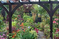 View through arch of oriental themed garden with conifers, Azaleas, Acers - Four Seasons Garden, Walsall