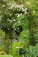 White bistro styled garden chair under rose arch with Alchemilla mollis and Digitalis purpurea