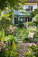 Stepping stones lead from the house to a round paved rest area with metal chair in a small garden with Rose 'Ballerina', Digitalis purpurea, Lobelia erinus, Lysimachia punctata, Nepeta Faassenii-Sorte and Petunia Surfinia
