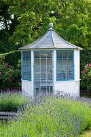 Blue and white summerhouse with lavender