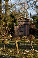 Wooden toadstool sculptures and one of the green oak temples, with Snowdrops in the Stumpery, Highgrove Garden, February 2011.