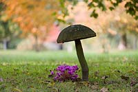 Cyclamen and giant wooden mushroom sculpture  in the Stumpery, Highgrove Garden, October, 2007.