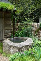 Well of water in front of stone crofter's hut - Naturally Dry, a William Wordsworth-inspired garden for Veolia. RHS Chelsea Flower Show 2012. Silver Flora medal winner