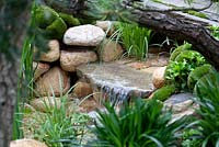 Moss mounds and decorative pebble waterfall in a traditional Japanese garden in the Satoyama district, Satoyama Life - Artisan Garden