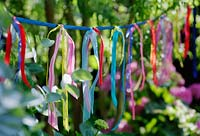 Home made garden bunting made from lengths of colourful ribbons knotted on to a length of ribbon