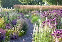 Border with Monarda 'Scorpion', Helenium 'Waltraud', Veronica 'Fascination', Sedum 'Karfunkelstein' and Calamagrostis 'Karl Foerster'
